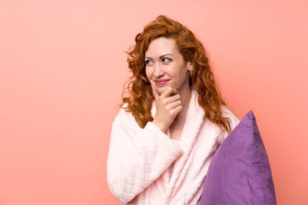 Redhead woman in dressing gown thinking an idea Banque d'images - 129856363