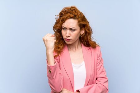 Redhead woman in suit over isolated blue wall with angry gesture Stock Photo