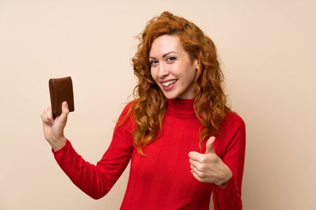 Redhead woman with turtleneck sweater holding a wallet