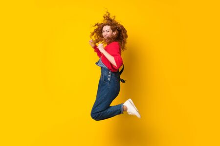 Redhead woman with overalls jumping over isolated yellow wall Stock fotó