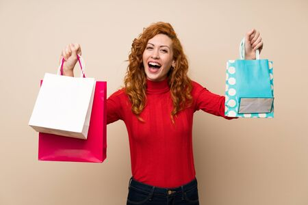 Redhead woman with turtleneck sweater holding a lot of shopping bags