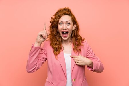 Redhead woman in suit over isolated pink wall with surprise facial expression Stock fotó