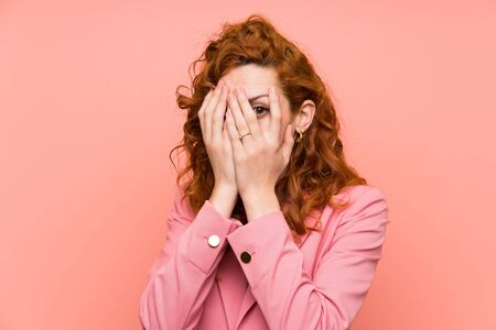 Redhead woman in suit over isolated pink wall covering eyes and looking through fingers