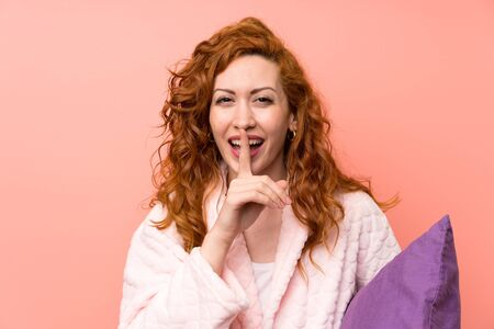Redhead woman in dressing gown doing silence gesture Banque d'images - 129856402