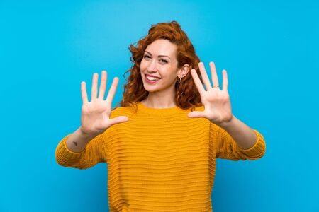 Redhead woman with yellow sweater counting ten with fingers