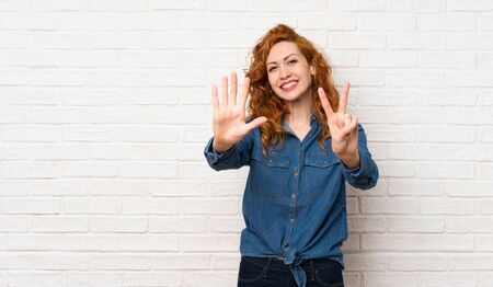 Redhead woman over white brick wall counting seven with fingers