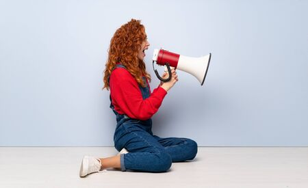 Redhead woman with overalls sitting on the floor shouting through a megaphone Stockfoto - 129920393