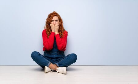 Redhead woman with overalls sitting on the floor nervous and scared putting hands to mouth