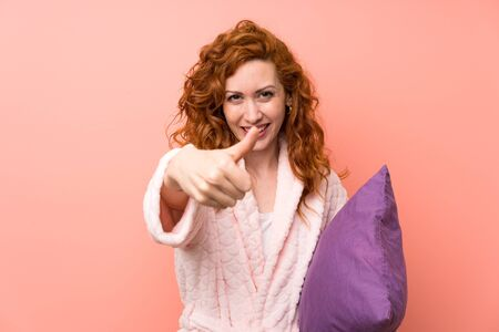 Redhead woman in dressing gown giving a thumbs up gesture Banque d'images - 129920569