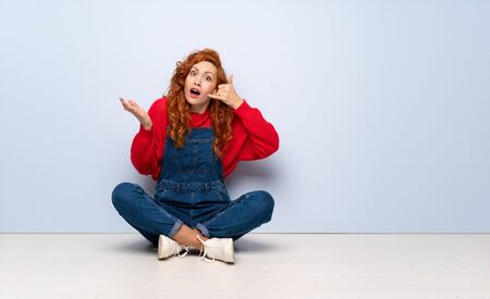 Redhead woman with overalls sitting on the floor making phone gesture and doubting 写真素材