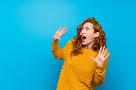 Redhead woman with yellow sweater nervous and scared Stockfoto