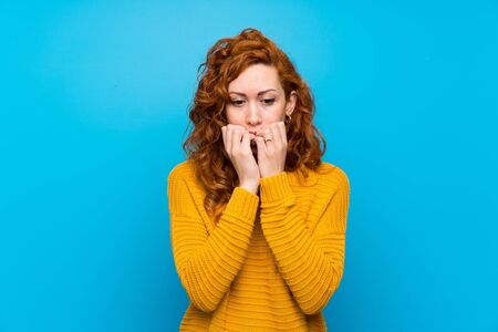 Redhead woman with yellow sweater nervous and scared putting hands to mouth Stockfoto