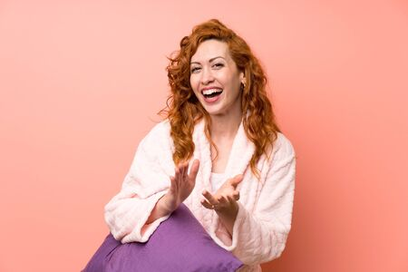 Redhead woman in dressing gown applauding Stock fotó