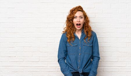 Redhead woman over white brick wall with surprise facial expression