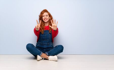 Redhead woman with overalls sitting on the floor counting seven with fingers