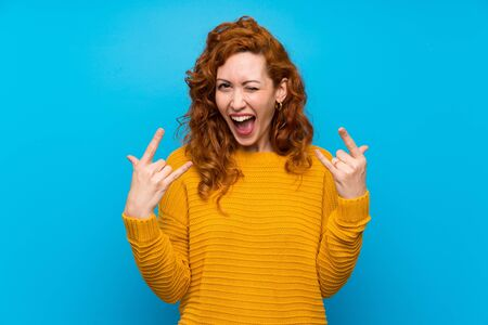 Redhead woman with yellow sweater making rock gesture