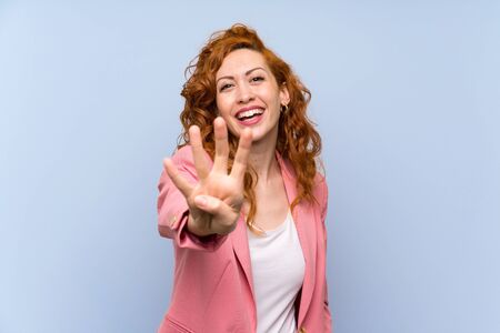 Redhead woman in suit over isolated blue wall happy and counting four with fingers Imagens