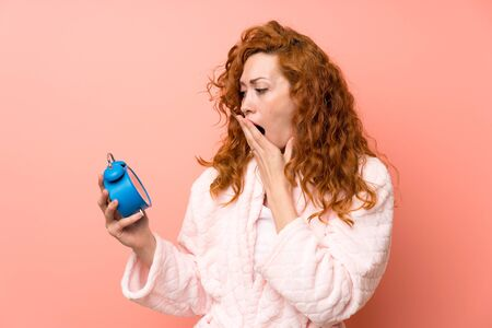 Redhead woman in dressing gown holding vintage clock and yawning