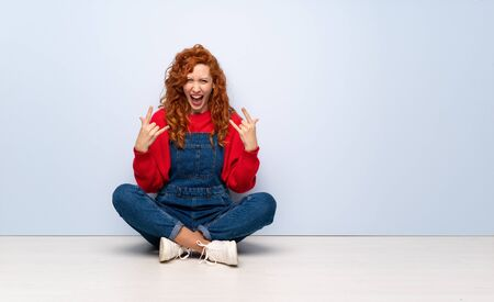 Redhead woman with overalls sitting on the floor making rock gesture Stockfoto