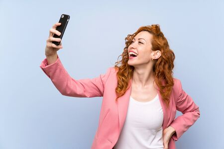 Redhead woman in suit over isolated blue wall making a selfie