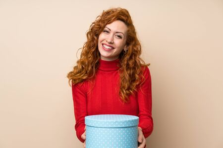 Redhead woman with turtleneck sweater holding gift box Imagens