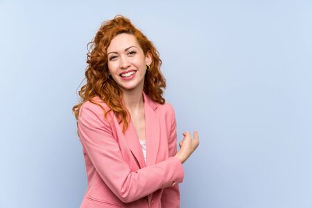 Redhead woman in suit over isolated blue wall pointing back Imagens
