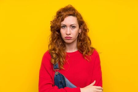 Redhead woman with overalls over isolated yellow wall sad