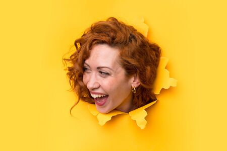 Happy Redhead woman through a hole paper Imagens