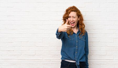 Redhead woman over white brick wall with thumbs up because something good has happened
