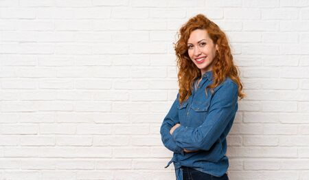 Redhead woman over white brick wall with arms crossed and looking forward Imagens