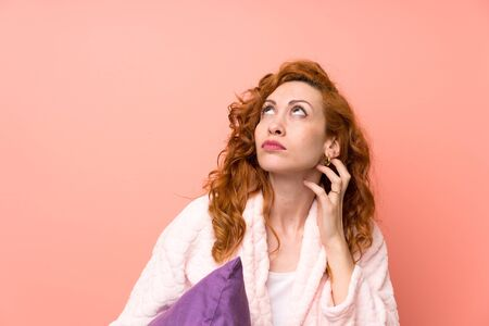 Redhead woman in dressing gown standing and thinking an idea
