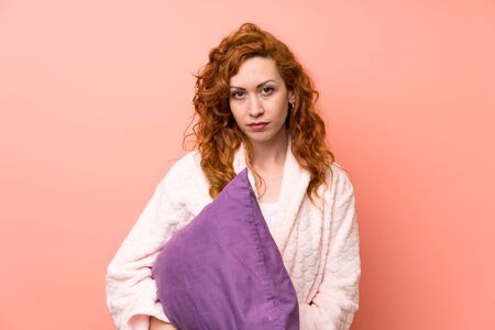 Redhead woman in dressing gown keeping arms crossed