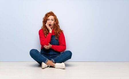 Redhead woman with overalls sitting on the floor surprised and shocked while looking right