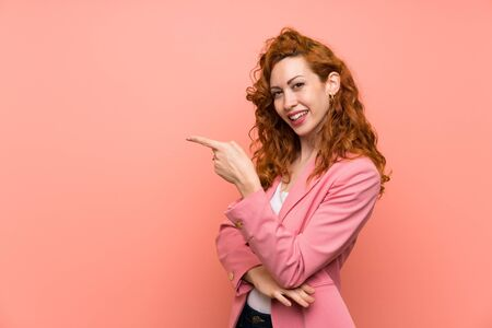 Redhead woman in suit over isolated pink wall pointing finger to the side