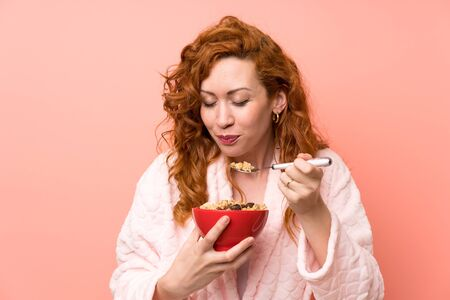 Redhead woman in dressing gown holding a bowl of cereals Imagens
