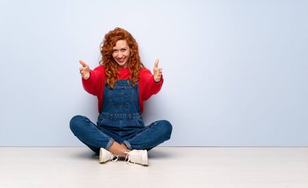 Redhead woman with overalls sitting on the floor presenting and inviting to come with hand Imagens