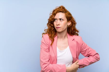 Redhead woman in suit over isolated blue wall with confuse face expression