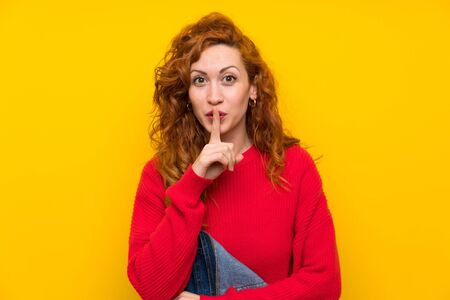 Redhead woman with overalls over isolated yellow wall doing silence gesture Imagens