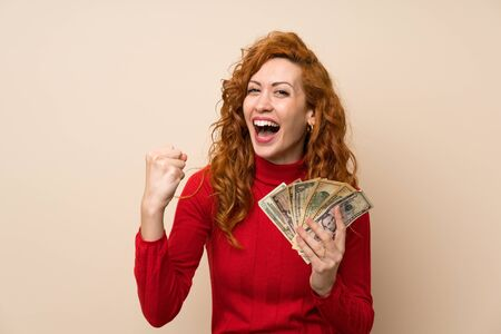 Redhead woman with turtleneck sweater taking a lot of money