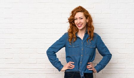 Redhead woman over white brick wall posing with arms at hip and smiling