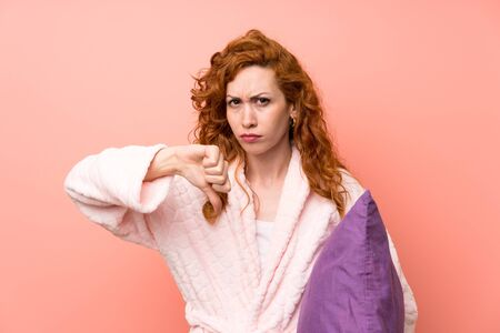 Redhead woman in dressing gown showing thumb down sign Banque d'images - 129921503