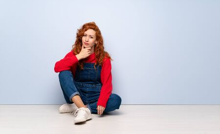 Redhead woman with overalls sitting on the floor thinking
