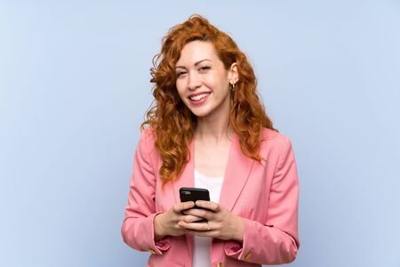 Redhead woman in suit over isolated blue wall sending a message with the mobile