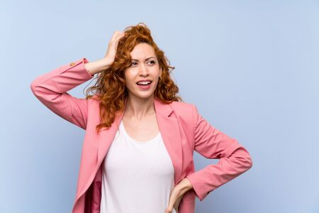 Redhead woman in suit over isolated blue wall having doubts while scratching head