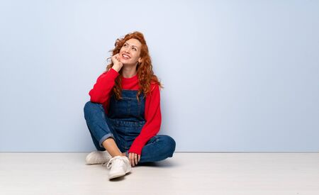 Redhead woman with overalls sitting on the floor thinking an idea while looking up