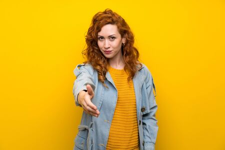 Redhead woman over isolated yellow background handshaking after good deal