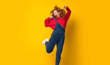 Redhead woman with overalls jumping over isolated yellow wall Imagens