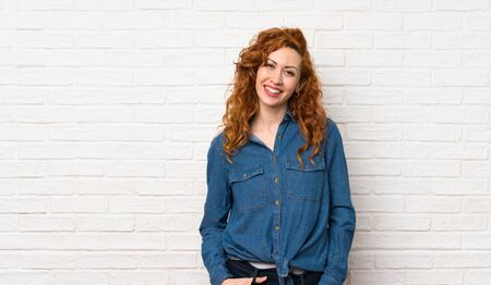Redhead woman over white brick wall laughing