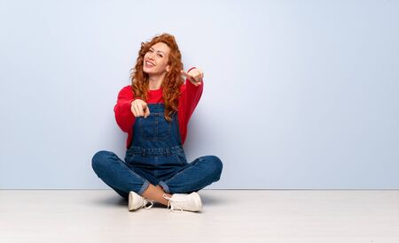 Redhead woman with overalls sitting on the floor points finger at you while smiling Imagens