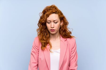Redhead woman in suit over isolated blue wall with sad and depressed expression